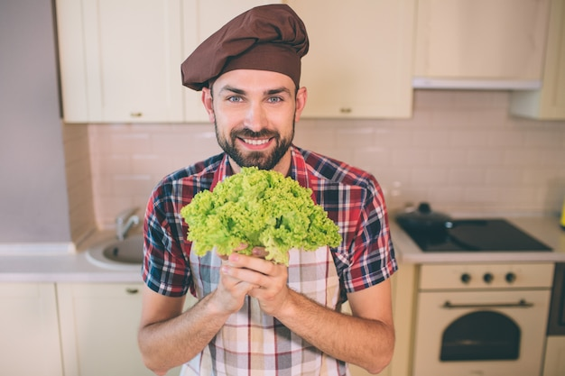 Nice and cheerful man stands and looks. he is happy. guy holds green letuce in hands. man poses. he looks amazing.