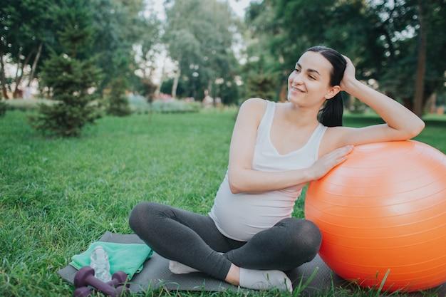 좋은 쾌활한 임신 한 여자는 공원 및 미소 요가 친구에 앉아. 그녀는 오렌지 휘트니스 볼에 몸을 기울입니다. 모델 휴식.