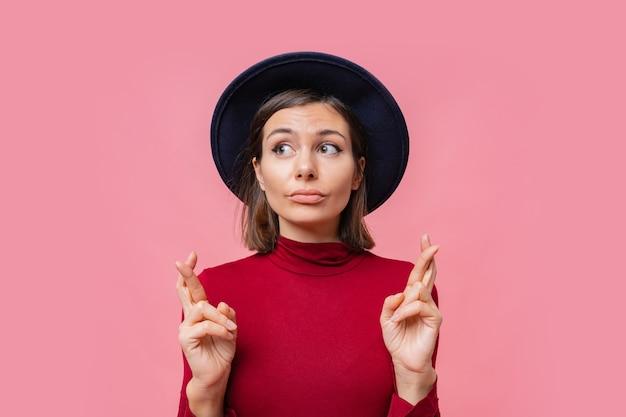 素敵な陽気な女性は彼女の指を交差させ続けるために最善を尽くしたいと思っています、最高の、孤立した赤いジャンパーを身に着けています