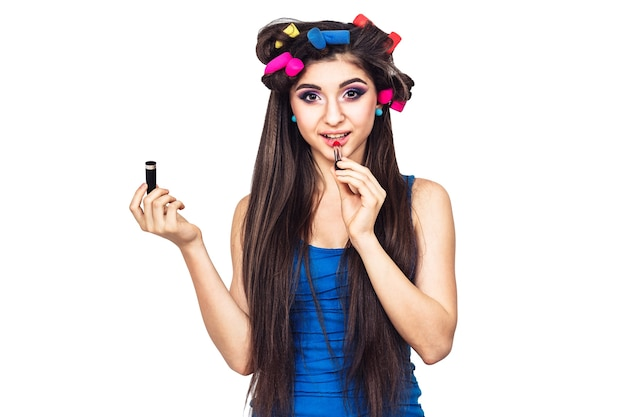 Симпатичная веселая молодая девушка в синем платье с бигуди для волос и с помадой в руке. женщина красит губы. изолированные на белой поверхности