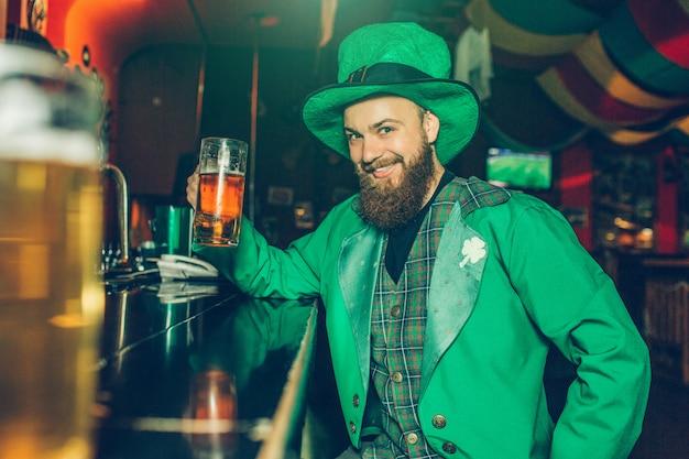 聖パトリックのスーツを着た素敵な陽気な若い男がパブのバーカウンターに座って、ビールのジョッキを保持しています。彼は見て笑います。幸せな男。