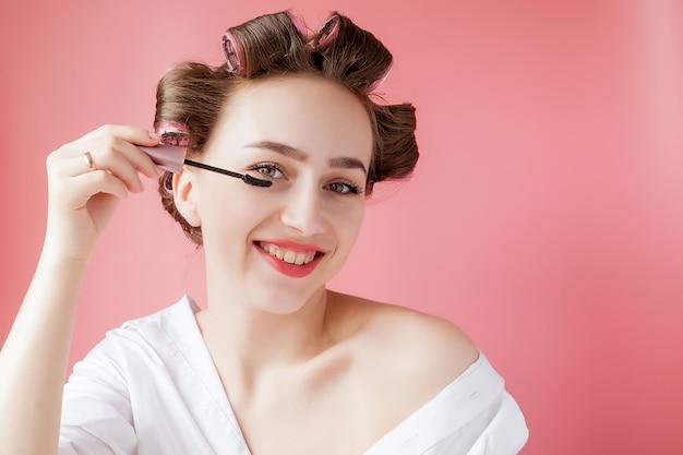 素敵な陽気な若いカーラーの女の子はピンクの背景に眉を描きます。