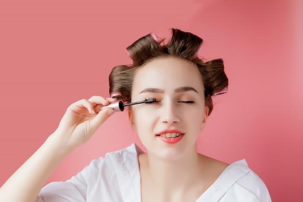 素敵な陽気な若いカーラーの女の子はピンクに眉を描く