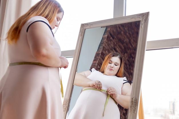 Симпатичная пухлая женщина измеряет свою талию, стоя перед зеркалом