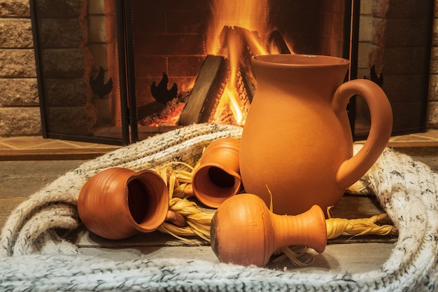 Nice clay pottery near cozy fireplace background, winter vacation, in country house.