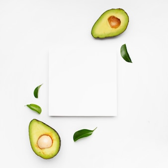 Nice composition of avocado on white surface with a frame for text