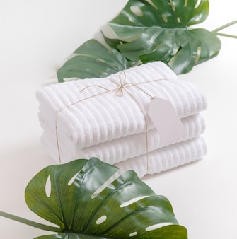 Nice composition with folded and stacked white terry towels with empty label and monstera leaves in tropical style against white background