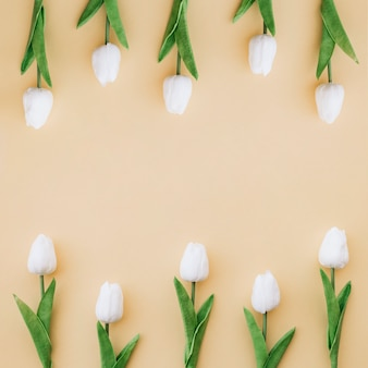 Nice composition with tulips on yellow background with space in the middle
