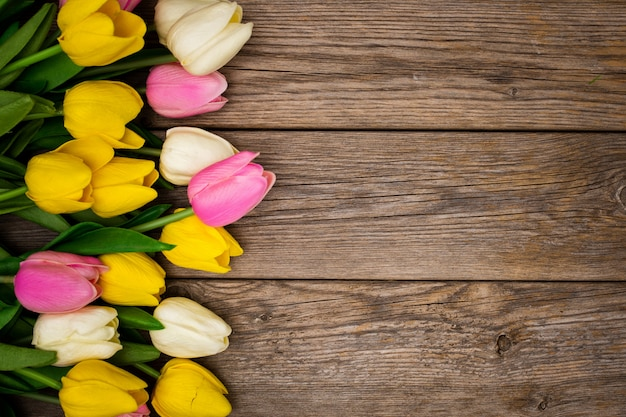 Nice composition with tulips with copy space on wooden