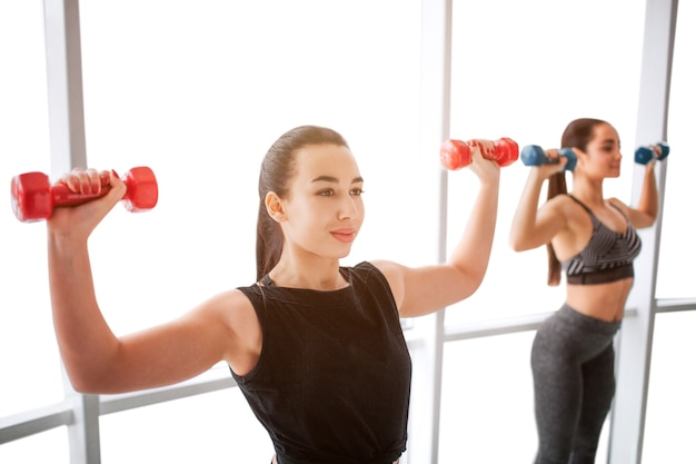 Nice and confident young women exercising with dumbbells at window. asian model stand in front and look forward. european young woman is behind and workout as well