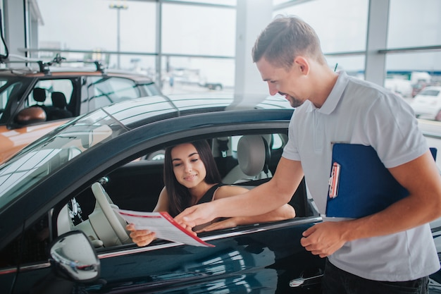 Nice consultant stands at black car and points on paper. he holds plastic tablet in other hand. nice and young woman sits in car and looks at document.