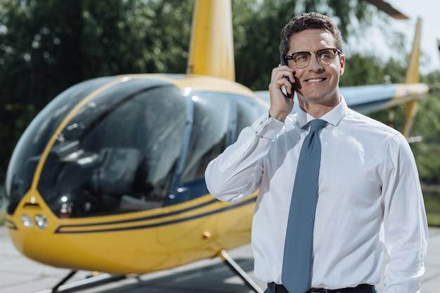 Хороший разговор. приятный молодой бизнесмен общается со своими партнерами по телефону и ждет отъезда