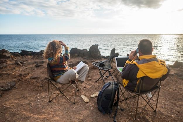 一日の終わりに日没を楽しんでいる素敵なカップルは、ラップトップとインターネット写真家へのモバイル接続を備えた代替オフィスで働く幸せな白人の人々のための放浪癖でライフスタイルを旅行します