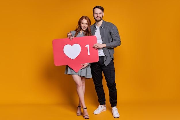 Славная пара мужчина женщина позирует с как знак в форме сердца, изолированные на оранжевом фоне.