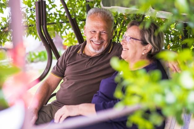 아름 다운 백인 수석 70 세의 좋은 부부는 미소와 웃음으로 재미 집에서 야외 앉아. 행복한 삶을 영원히 사랑하며 은퇴 한 시간을 즐기십시오. 남자에 초점