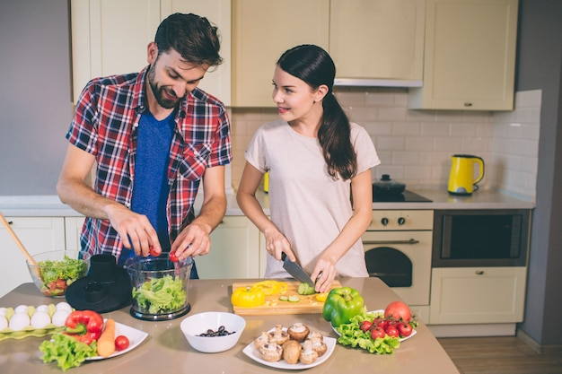 Nice couple works together in kitchen. she cuts mushrooms and look at guy.