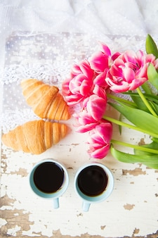 Nice cup of coffee, croissants and pink tulips on old white table, close-up