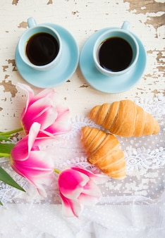 Nice cup of coffee, croissants and pink tulips on old white table