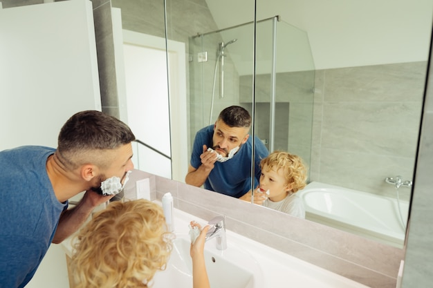 Nice cute father and son looking into the mirror