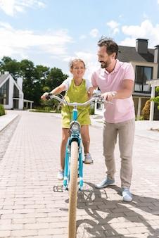 자전거 타기를 즐기면서 웃 고 좋은 귀여운 소녀