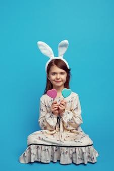 Хороший милый ребенок девочка, имеющая два печенья в форме сердца на палочках