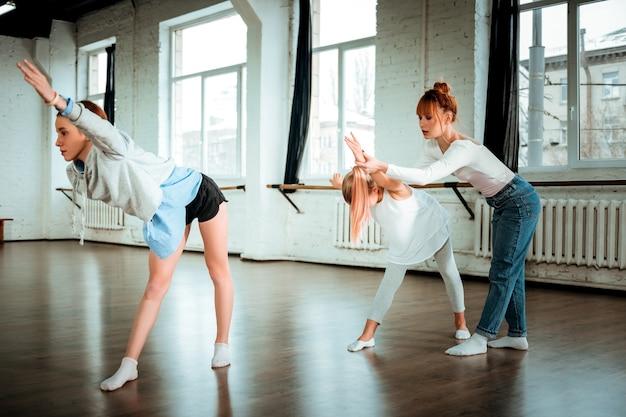 素敵なダンスの先生。学生と一緒に働いている間関与しているように見える赤い髪のプロのモダンダンスの先生