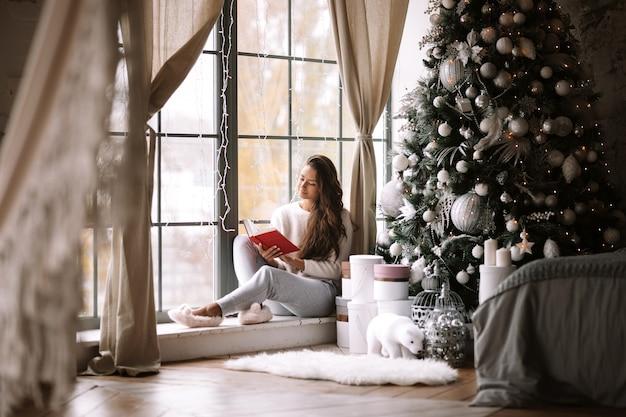바지, 스웨터, 따뜻한 슬리퍼를 입은 멋진 검은 머리 소녀는 새해 나무, 선물, 양초 옆에 있는 탁 트인 창문의 창턱에 앉아 책을 읽습니다.