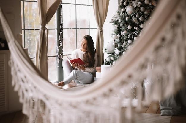 바지, 스웨터, 따뜻한 슬리퍼를 입은 멋진 검은 머리 소녀가 새해 나무와 선물 옆에 해먹이 있는 방의 탁 트인 창문 창턱에 앉아 책을 읽습니다.