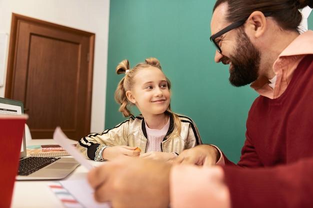 좋은 날. 학교에서 수업을 듣는 동안 만족감을 느끼는 그녀의 손에 팔찌가 달린 귀여운 국방과 소녀