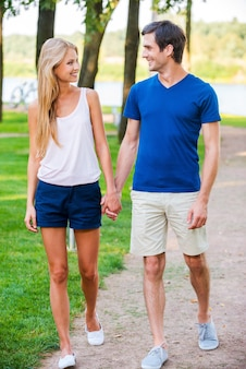 Nice day for date. full length of beautiful young loving couple walking along the park road and looking at each other with smile
