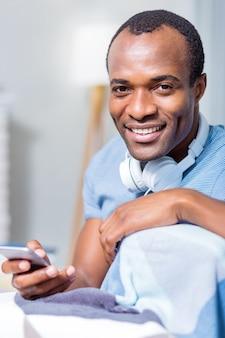 Хороший довольный позитивный мужчина улыбается и использует свое технологическое устройство, находясь в позитивном настроении