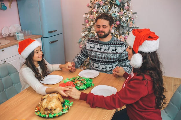 Nice and delightful members of family sitting at table and playing. they hold each other's hands and keep eyes closed. they pray before eating festive food.