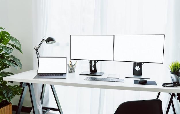 집, 컴퓨터 및 노트북의 멋진 책상이 오후에 빛을 발했습니다.