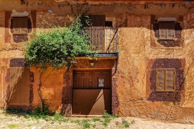 입구에 다채로운 식물과 꽃이있는 석조 주택의 멋진 외관.