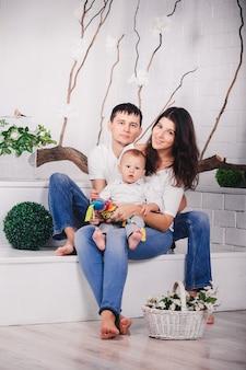 실내 밝은 현대적인 인테리어에 스튜디오 배경에서 좋은 가족. 젊은 어머니와 아버지가 함께 포즈를 취하고 소파에 앉아 자식 아들과 함께 웃고.