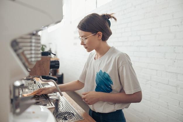 カフェテリアでコーヒーマシンを掃除する素敵な女性のバリスタ