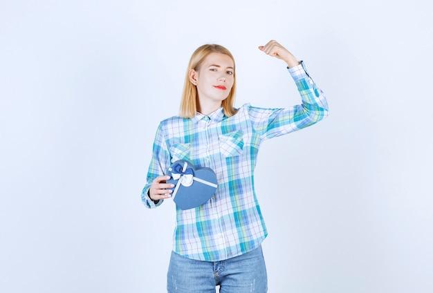 Милая блондинка демонстрирует свою силу, держа синий подарок перед белой стеной