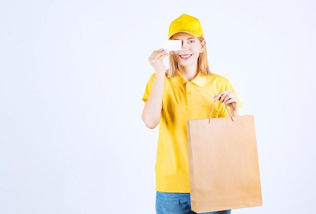 ショッピングバッグを持ち上げている間、彼女の右目の前に彼女のカードを持っている素敵な女性の宅配便