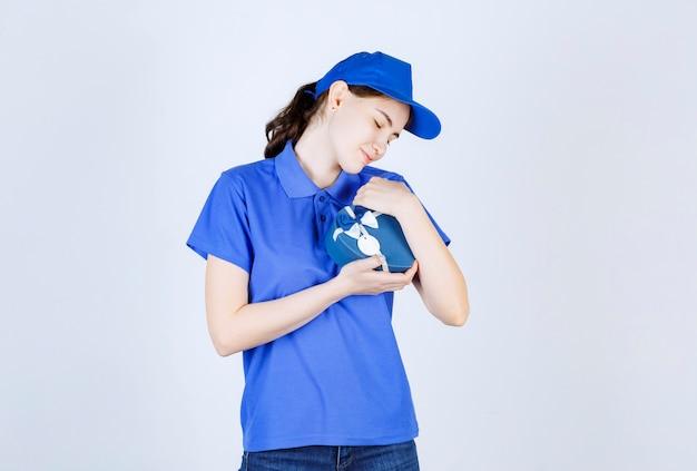 頭を左に傾けながら両手でギフトボックスを持っている青い帽子の素敵な女性の宅配便