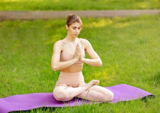 Красивая женщина медитирует в свежем весеннем саду