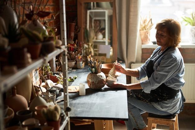 도자기 스튜디오에서 테이블에 앉아있는 동안 그릇과 페인트 브러시를 들고 앞치마에 좋은 여성 포터