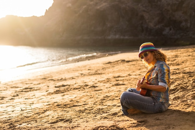 Красивая свобода хиппи дама в отпуске поет песню на открытом воздухе на пляже во время заката
