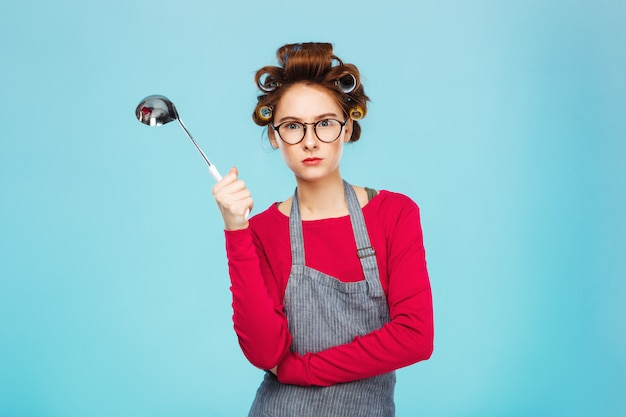 Nice funny girl hides from dangerous ladle and standing on blue wall