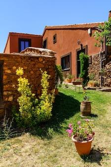 입구에 다채로운 식물과 꽃이있는 오래된 집의 멋진 정원.