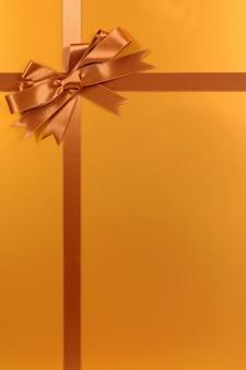 L'oro regalo di natale di fondo con fiocco