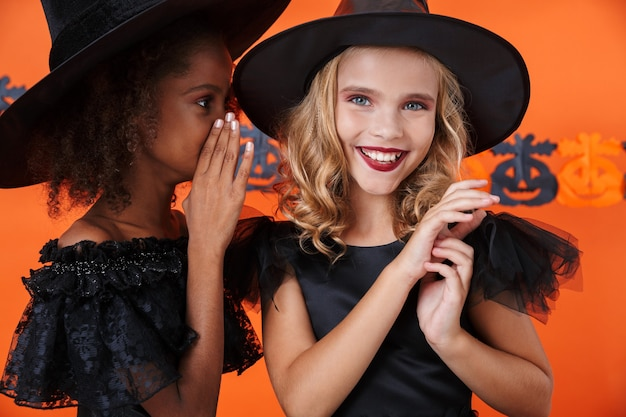Nice girl in black halloween costume whispering secret to smiling friend in her ear isolated over orange pumpkin wall