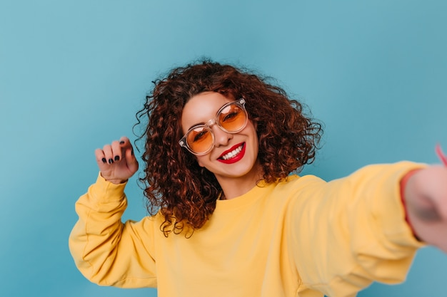 Nice girl in bright orange sunglasses and with bright lips posing on blue space. woman in yellow top takes selfie.