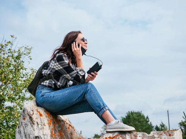 A nice girl in a casual plaid shirt, jeans and glasses is talking on a phone connected to a power bank