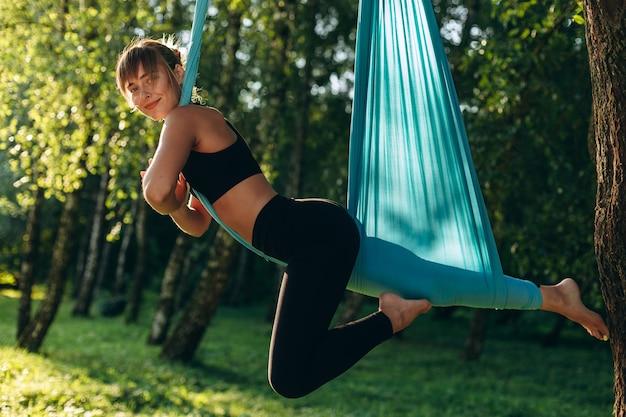 Симпатичная девочка занимается летной йогой в парке на открытом воздухе. счастливо глядя в камеру