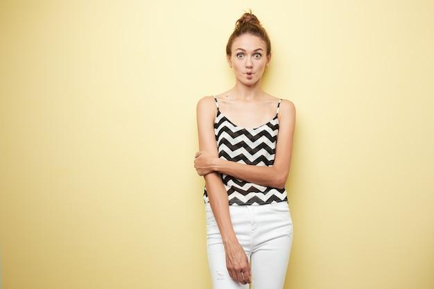 Милая девушка в полосатом топе и белых джинсах скромно стоит на желтом фоне
